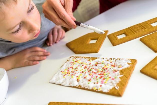 Mani del bambino che decorano biscotti di panpepato, concetto di gioco sensoriale per bambini