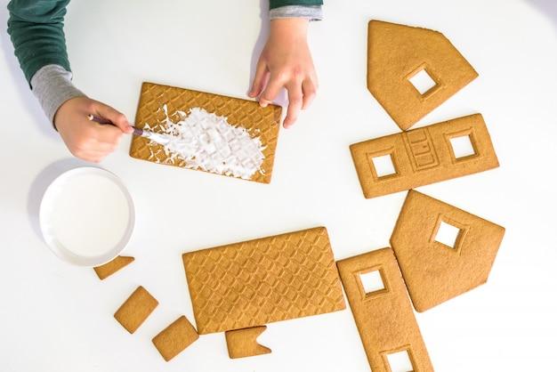 Mani del bambino che decorano i biscotti di pan di zenzero, gioco sensoriale per bambini