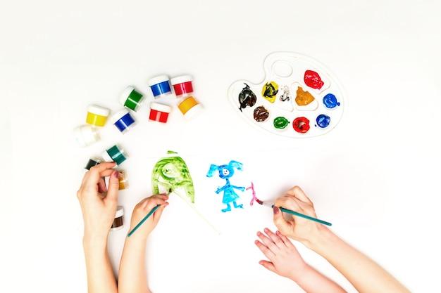 Mani del bambino che dipingono una famiglia