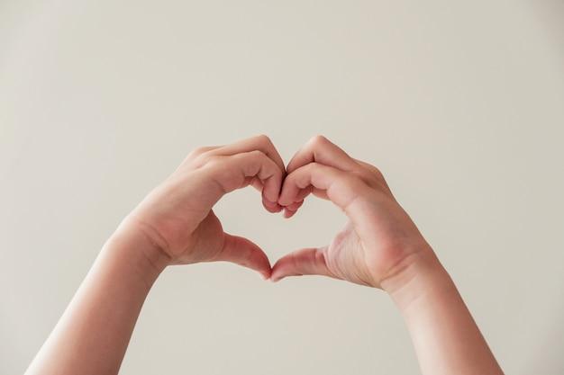 Mani del bambino che fanno forma del cuore, salute del cuore, donazione, carità volontaria felice