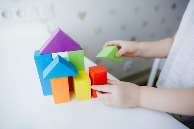 Mani del bambino che giocano con i mattoni di legno variopinti sulla linguetta bianca