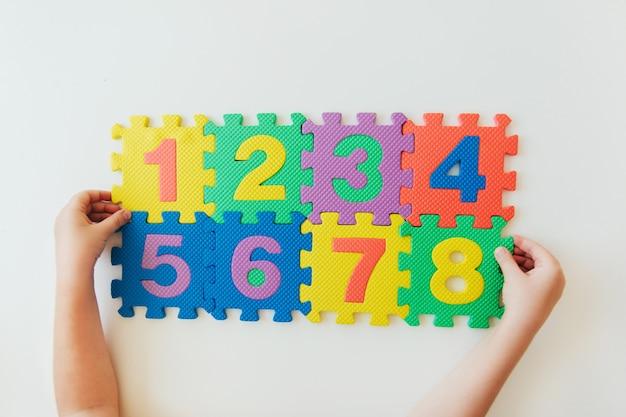 Mani del bambino che giocano con i numeri, imparando la semplice moltiplicazione