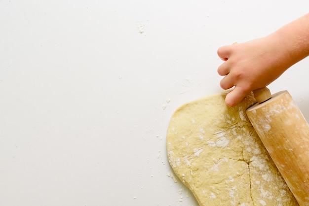 Mani del bambino che impastano una pizza con il mattarello.