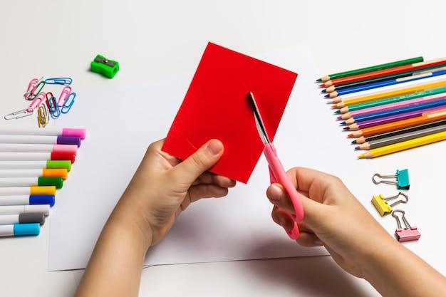 Mani del bambino che tagliano un cuore rosso di carta