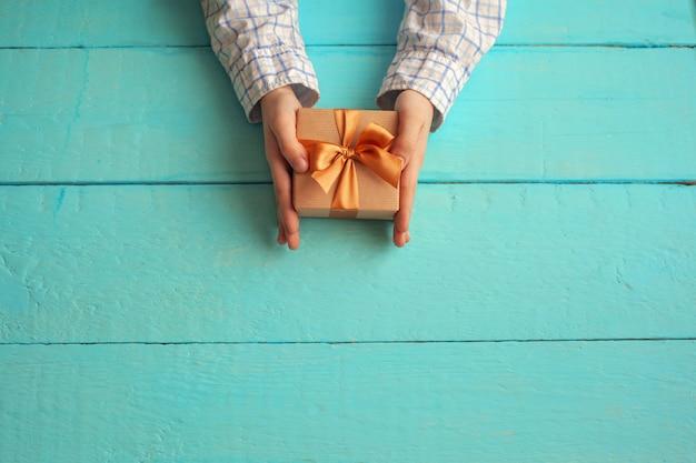 Mani del bambino che tengono confezione regalo avvolto in carta artigianale e legato con fiocco.