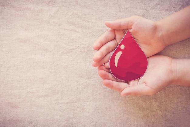 Mani del bambino che tengono goccia di sangue
