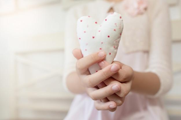 Mani del bambino che tengono un cuore di cotone. san valentino .