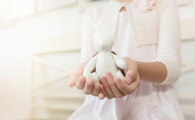 Mani del bambino che tengono un orso di cotone, un fuoco selettivo e un colore tonificati. san valentino .
