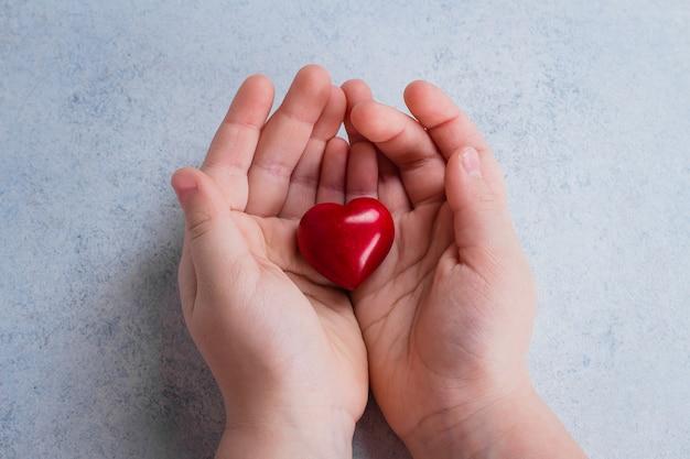 Mani del bambino che tiene cuore rosso