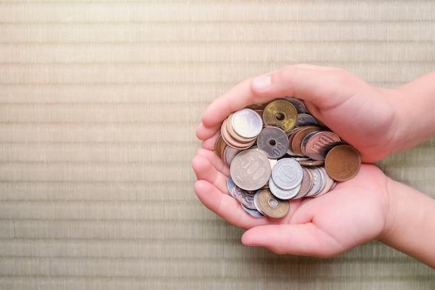 Mani del bambino con denaro giapponese