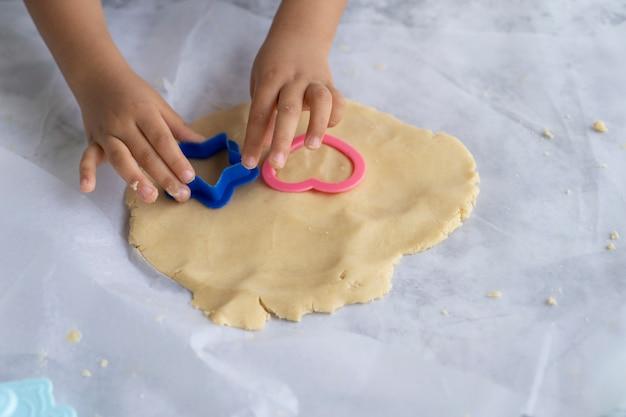 Mani del bambino con formina per biscotti