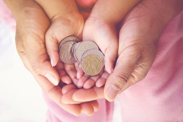 Mani del bambino della tenuta del genitore con le monete dei soldi, concetto di risparmio