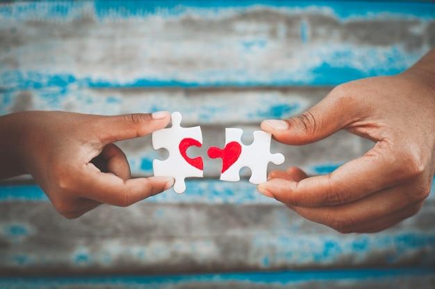 Mani del bambino e del genitore che collegano il pezzo del puzzle delle coppie con il cuore rosso tirato