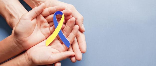 Mani del bambino e dell'adulto che tengono carta a forma di nastro blu e gialla, consapevolezza di sindrome di down, giornata mondiale della sindrome di down