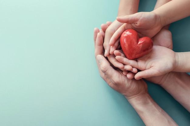 Mani del bambino e dell'adulto che tengono cuore rosso sul fondo dell'acqua