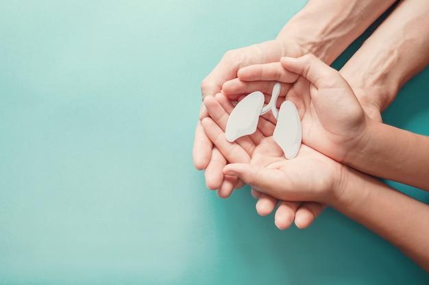 Mani del bambino e dell'adulto che tengono polmone, giornata mondiale della tubercolosi, giornata mondiale senza tabacco, virus corona covid-19, inquinamento atmosferico ecologico; concetto di donazione di organi