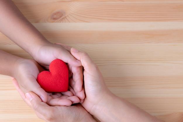 Mani del bambino e della donna che tengono cuore rosso per la giornata mondiale del cuore o la giornata mondiale della salute