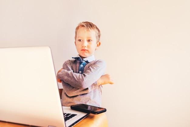 Mani del bambino sulla tastiera del computer portatile accanto a un telefono cellulare per fare affari.