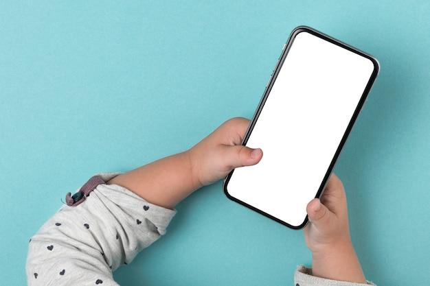 Mani del bambino usando il telefono mock up