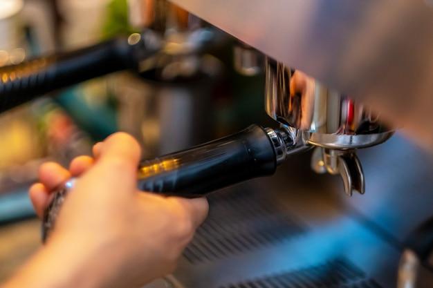 Mani del barista che fanno il caffè dalla macchina.