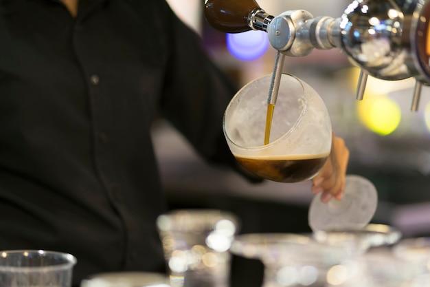 Mani del barista che versano una birra nera in un bicchiere.