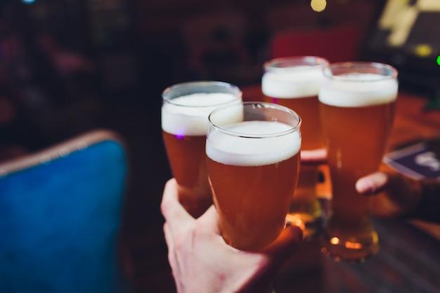 Mani del barista versando una birra chiara in un bicchiere.
