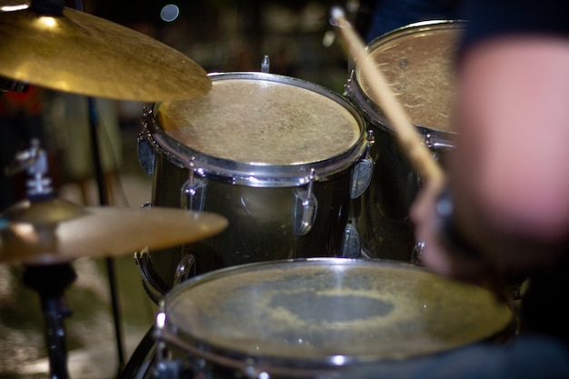 Mani del batterista con il primo piano di bastoni e tamburi