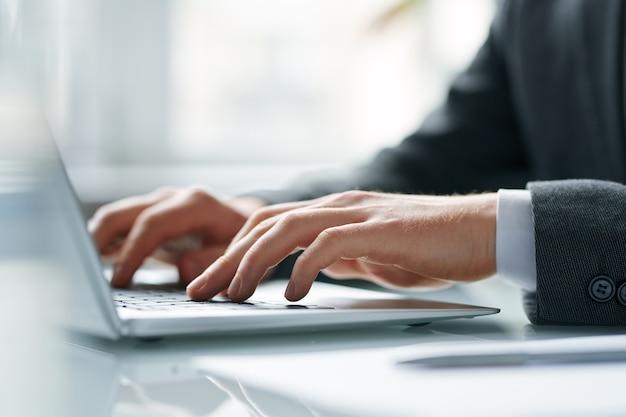 Mani del broker mobile contemporaneo che spinge i tasti della tastiera del laptop mentre svolge il suo lavoro