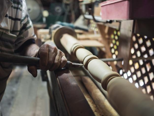 Mani del carpentiere che gira legno sul tornio
