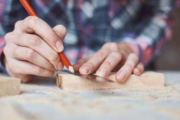 Mani del carpentiere che prendono misurazione con la matita del pezzo di legno