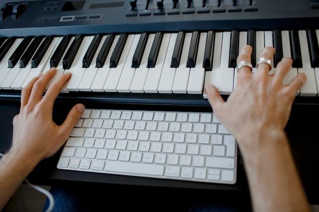 Mani del compositore sui tasti del piano in studio di registrazione. tecnologia di produzione musicale, l'uomo sta lavorando al pianino e alla tastiera del computer sulla scrivania. concetto da vicino.