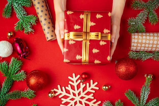 Mani del contenitore di regalo di natale della holding della donna con gli ornamenti di natale