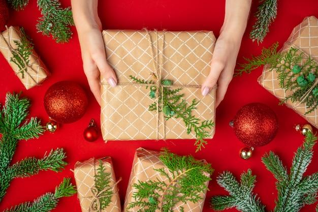 Mani del contenitore di regalo di natale della holding della donna su una priorità bassa rossa