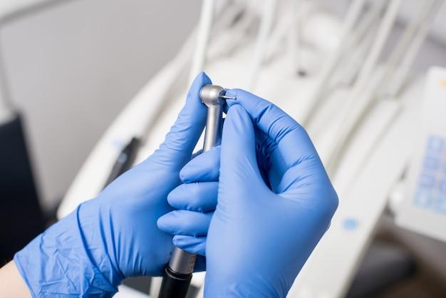 Mani del dentista con guanti blu