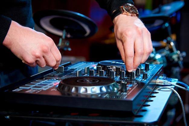 Mani del dj dietro il pannello di controllo sullo sfondo del set di batteria
