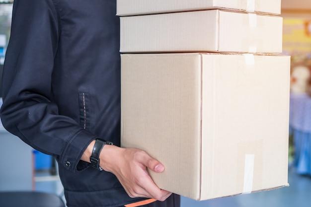 Mani del fattorino che tengono le scatole del pacchetto