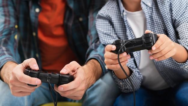 Mani del figlio e del padre che giocano sulla console