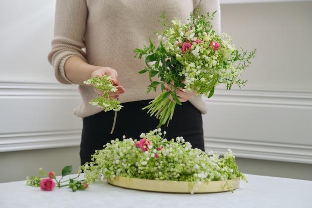 Mani del fiorista della donna che fanno mazzo di fiori