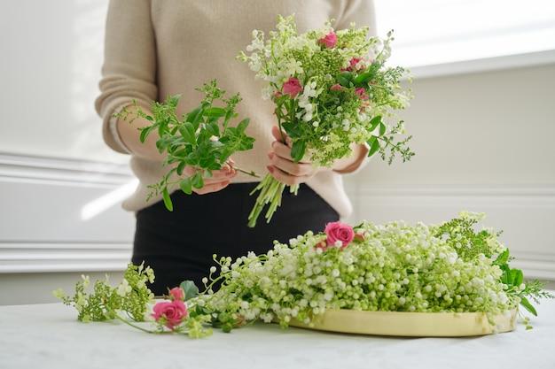 Mani del fiorista donna che fanno il mazzo di fiori rose rosa, mughetto fresco.