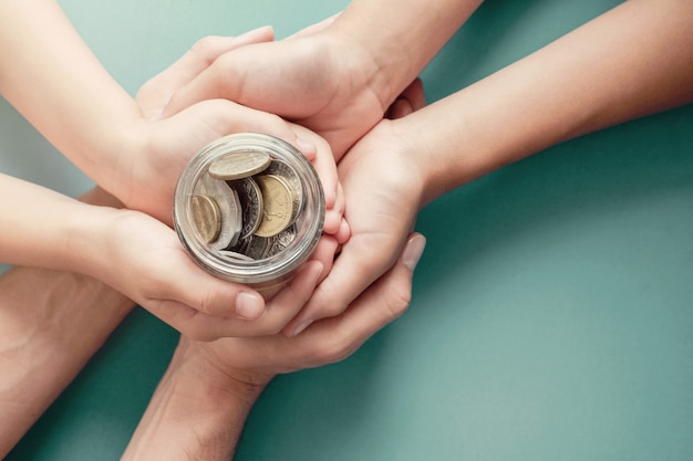 Mani del genitore e del bambino che tengono il barattolo dei soldi, donazione, risparmio, carità, concetto di piano di finanze familiari