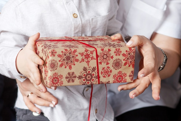 Mani del genitore e del bambino che tengono un contenitore di regalo di natale. felice anno nuovo e concetto di natale. vacanze invernali