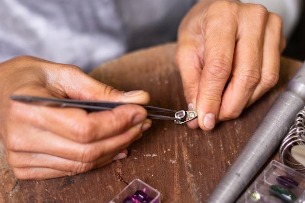 Mani del gioielliere che mettono un gioiello sull'anello
