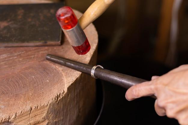 Mani del gioielliere che misurano un anello