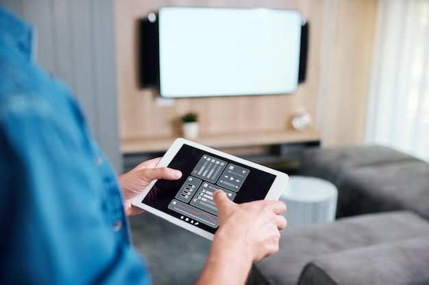 Mani del giovane che tiene tablet con sistema di controllo remoto intelligente durante la regolazione del volume o la scelta del canale