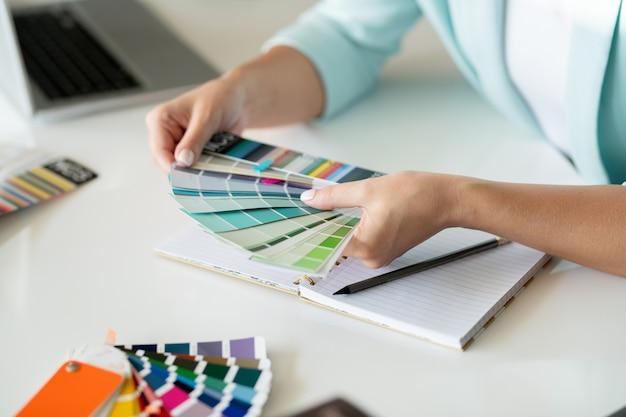 Mani del giovane designer creativo con campioni che scelgono i colori per la nuova collezione sulla scrivania