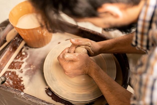 Mani del giovane maestro al centro della ruota di ceramica rotante durante il lavoro su una nuova pentola o altro oggetto di terracotta