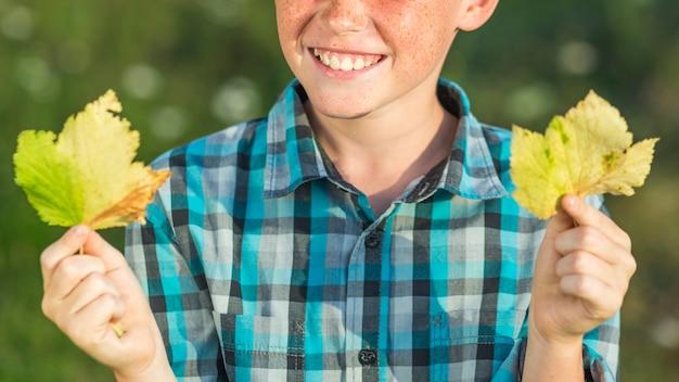 Mani del giovane ragazzo di smiley con i fogli di autunno