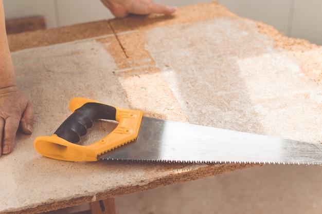 Mani del lavoratore con una tavola di legno, visto in officina.