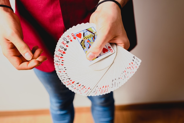 Mani del mago facendo trucchi con un mazzo di carte.