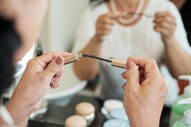 Mani del mascara senior irriconoscibile che tengono mascara davanti allo specchio